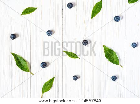 Blueberries and leaves on white wooden background. Ripe and juicy fresh picked bilberries close up. Top view or flat lay