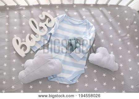 Cute knitted baby toy with bodysuit, decor and pillows in crib