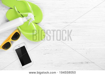Summer vacation concept. Flip-flops, mobile phone, bottle and sunglasses on white wooden background