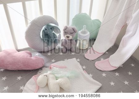 Adorable handmade crochet toys with baby clothes, pillows and bottle of milk in crib