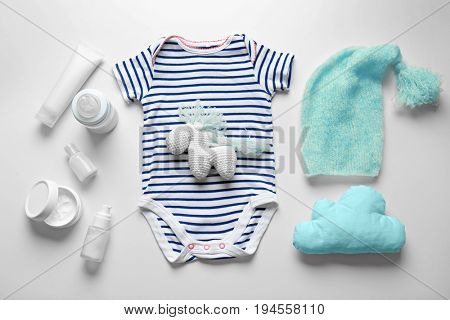 Composition of bodysuit, crochet toy, pillow and baby care accessories isolated on white