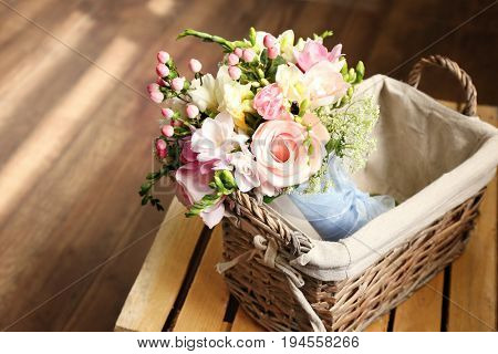 Beautiful bouquet with freesia flowers in basket on wooden crate