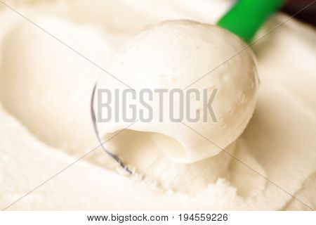 Tasty vanilla ice cream scooped out of container with utensil