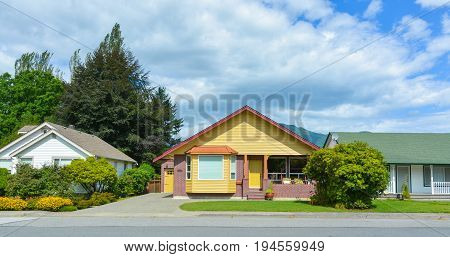 Bright yellow house with accurate lawn in front and concrete driveway to the garage