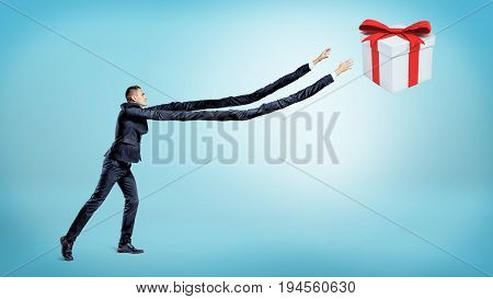 A businessman with extremely long arms trying to catch a gift box on blue background. Bait and hook. Gifts and best deals. Greed and profit.