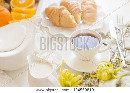 Continental Breakfast With Gold French Croissants Fruits And Cup Of Tea On White Table In A Morning