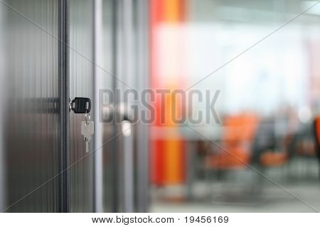 Bookcase and keys in modern office (soft focus)