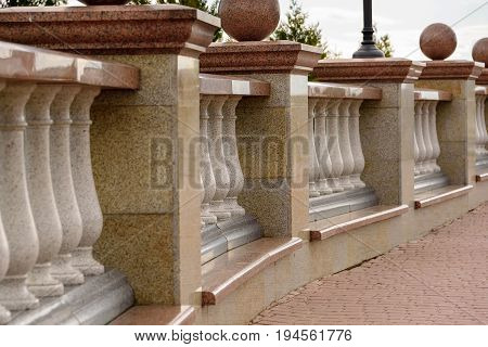 Stone balustrade from granite and pavement close-up.
