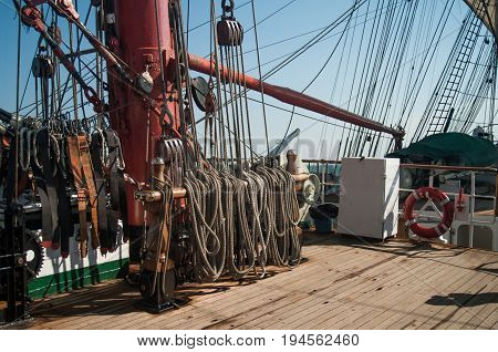 Part of wooden sailboat deck with base of mast, blocks, ropes and other rigging
