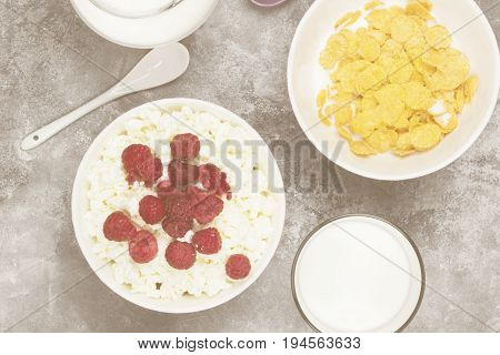 Cottage Cheese In Bowl With Frozen Raspberry And Cup Of Cornflakes, Milk In Glass On A Light Backgro
