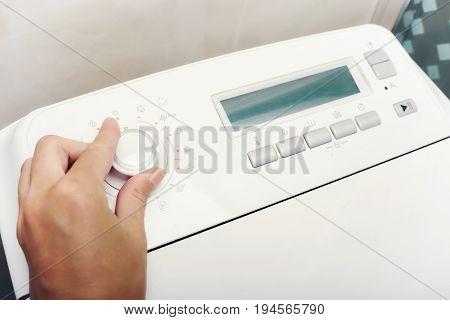 Close Up of woman's hand choosing cycle crogram on washing machine