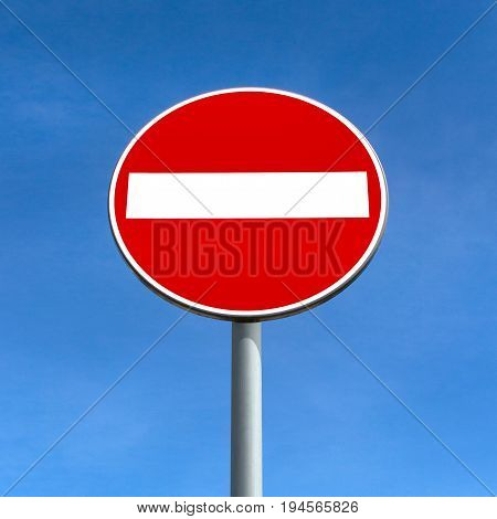 Round red road sign on metal pole. No Entry road-sign over blue sky.