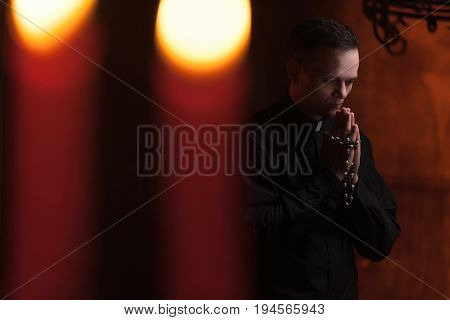 Praying Priest. Portrait Of Priest Next To The Candles Prays