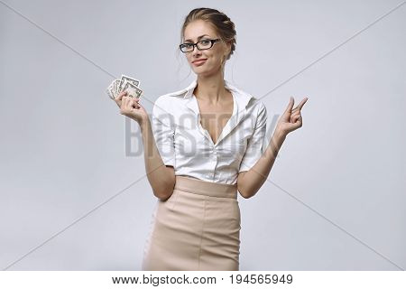 A business lady in glasses and white shirt holds a little money in her right hand and her left hand shows that there is very little money. The concept of a small salary an inadequate remuneration or bad economics or crisis.