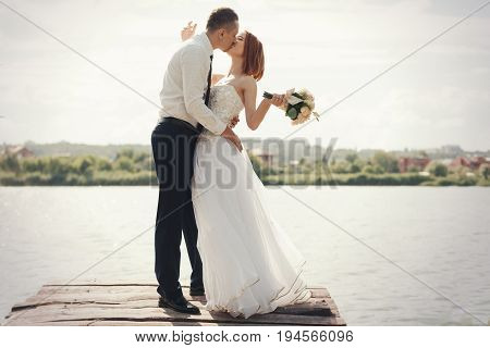 Wedding Couple Walking On Bridge Near Lake On Sunset At Wedding Day. Bride And Groom In Love