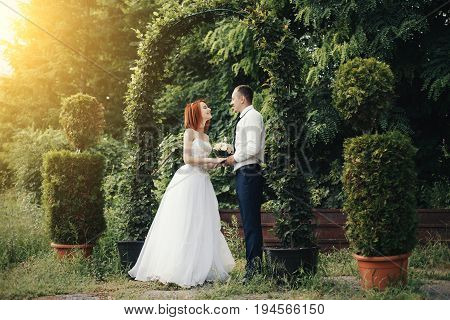 Handsome groom in white shirt and tie holds the bride's hand near green flower archway with beautiful sunset on the background