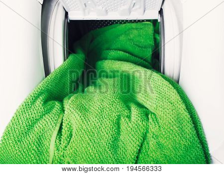 Close Up of green towel getting out from washing machine
