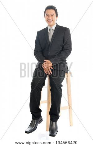 Full body portrait of happy young Southeast Asian businessman sitting on high chair, isolated on white background.