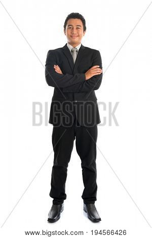 Full body front view of arm crossed young Southeast Asian businessman standing isolated on white background.