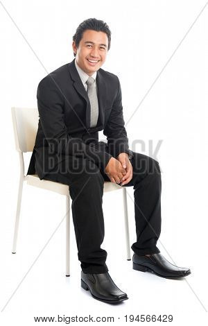 Full body portrait of attractive young Southeast Asian businessman sitting on a chair, isolated on white background.