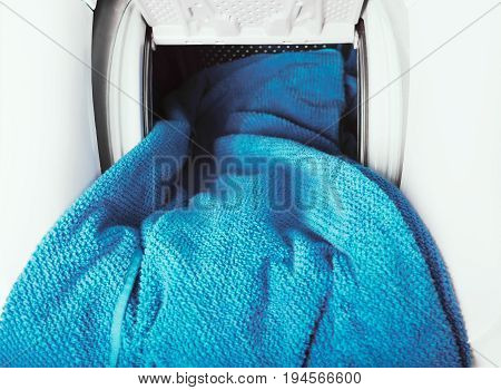 Close Up of blue towel getting out from washing machine