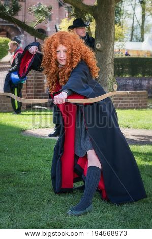 Haarzuilens, Netherlands - April 24 2016: Red hairy girl with handbow and magic wand on The Elf Fantasy Fair (Elfia) an outdoor fantasy event in the Netherlands.
