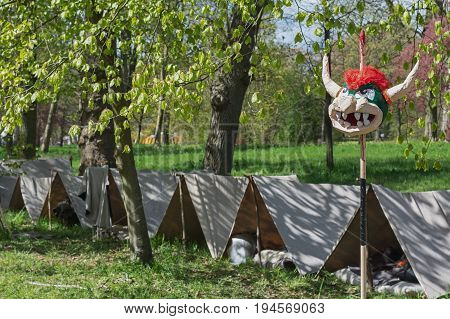 Simple tents on the festival site with in front an impaled bullhead of papier mache.