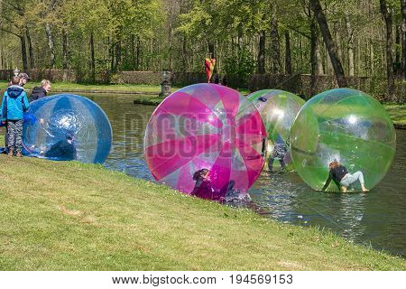 Haarzuilens, Netherlands - April 24 2016: Children play in large plastic balls on the pond of the park