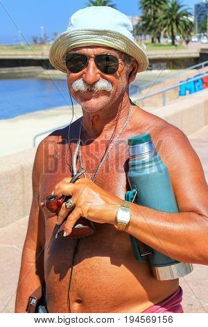 MONTEVIDEO URUGUAY-DECEMBER 9: Unidentified man stands with mate cup and thermos at the beach on December 92014 in MontevideoUruguay. Mate is a traditional South American drink.