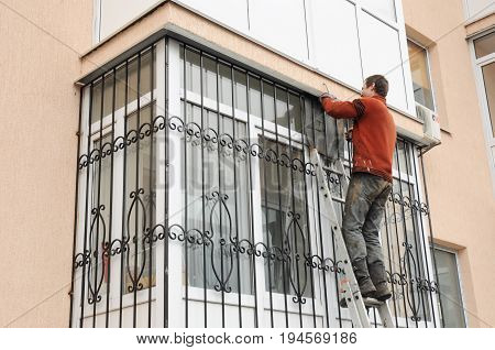 KYIV UKRAINE - AUGUST 16, 2017:  Worker install window iron security bars for house safety. Contractor installing window iron security bars with welding. Security Shutters Grilles Installation.