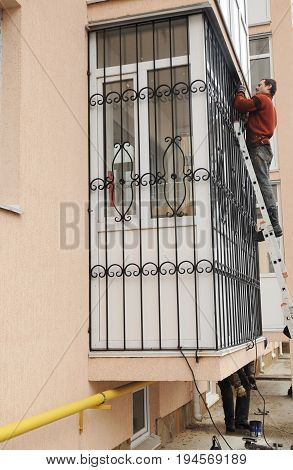 KYIV UKRAINE - JULY 13 2017:  Security Shutters Grilles Installation. Worker install window iron security bars for house safety. Contractor installing window iron security bars with welding.
