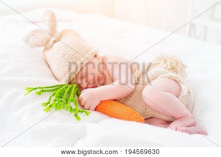 Very cute Two weeks old smiling newborn baby boy wearing knitted bunny costume, hat with rabbit ears, tail and funny carrot toy. Sweet new born baby portrait sleeping in his bed