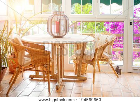 Restaurant interior. Fashioned terrace. View of a sunny empty summer cafe terrace with table and wicker chairs. Interior of cozy restaurant decorated