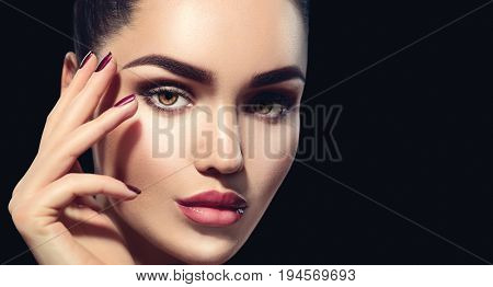 Beauty Brunette Woman with Perfect Makeup. Beautiful Professional Holiday Make-up. Lips and Nails, perfect eyebrows shape. Beauty Girl's Face isolated on black background