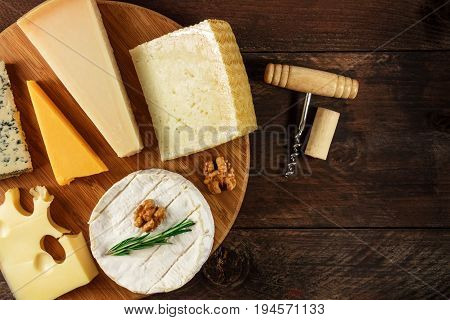 An overhead photo of a selection of cheeses, shot from above on a rustic texture, with a wine corkscrew and a cork, and a place for text