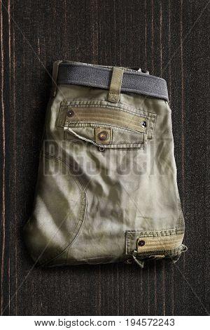 Folded khaki trousers on dark wooden background