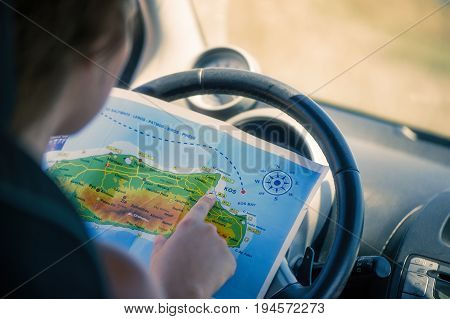 A young woman is driving a car and looking at the map. Map of the Greek island of Kos. The capital of Kos