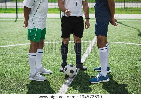 Cropped Shot Of Referee And Soccer Players On Soccer Pitch Starting Game