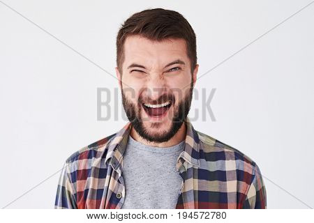 Close-up shot of screaming emotional young bearded man posing isolated over white background
