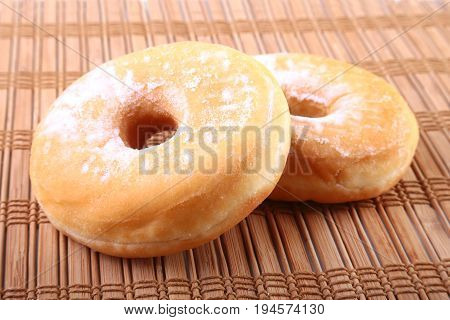 Homemade Doughnuts with Jelly filled and powdered sugar on Bamboo tablecloth. Selective focus