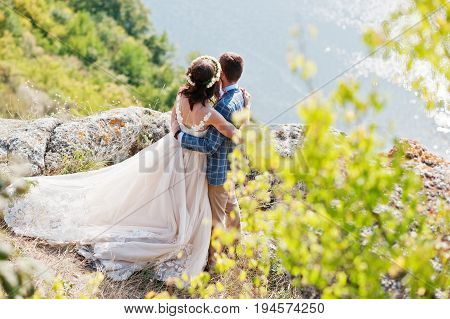 Newlywed Standing Next To Green Bushes On The Precipice With A View Of A Lake In The Background On T
