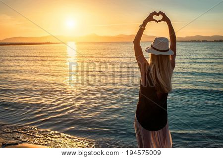 Blonde woman in summer hat stay on the coastline by sea beach with heart symbol of her hands. Sea sunset view. Freedom. Wind. Summer. Beach. Sunset. Vacation. Looking to a sky and sea. Looking forward