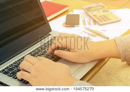 accountant or business man working with laptop computer report sheet calculator smartphone notebook and pen finances and calculate on desk savings business economy concept sunlight effect
