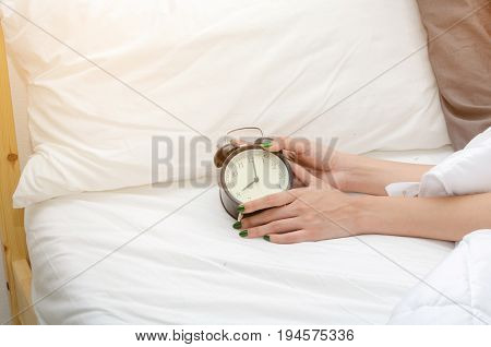 close up woman hand reaching out for alarm clock times at 7 o'clock morning on bed in bedroom at the morning with sunlight effect soft focus