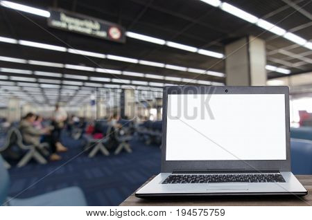Laptop computer with white blank screen on wooden table with blurred view of passenger waiting in the airport terminal copy space working outside office online social media searching data concept