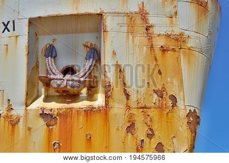 Old rusty anchor on the side of and old metal shipwreck in the dock