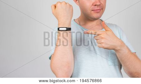 Cheerful young man standing and pointing on fitness tracker over grey background.