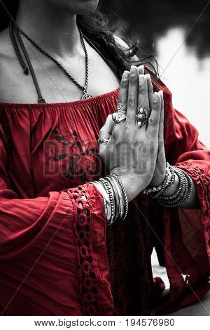 woman hands in yoga symbolic gesture mudra wearing red tunic and lot of bracelets and rings outdoor closeup  summer day