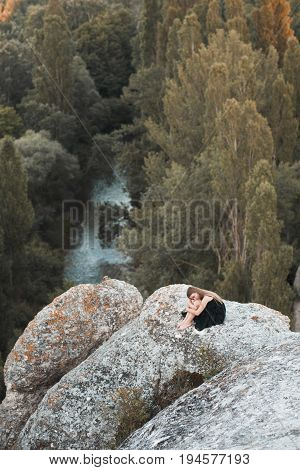 Abandoned teen girl 14-16 year old sitting on rocks over beautiful nature view. Loneliness. Sadness.