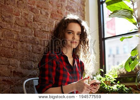 Handsome student female holding cell phone using photo editing apps posting new pics via social networks or sending quick instant messages to friends sitting among plant pots looking at the camera